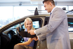 Happy woman with car dealer in auto show or salon Stock Photos