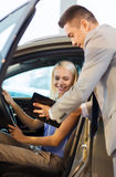 Happy woman with car dealer in auto show or salon Stock Photo