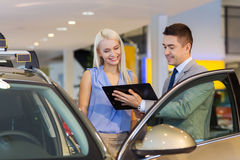 Happy woman with car dealer in auto show or salon Royalty Free Stock Photography