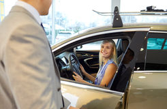 Happy woman with car dealer in auto show or salon Stock Images
