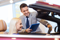 Happy woman with car dealer in auto show or salon. Auto business, car sale, technology and people concept - happy women and car dealer with tablet pc computer in stock photo
