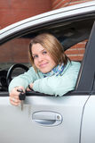 Happy woman in car with ignition key. Happy Caucasian woman in vehicle window with car key Royalty Free Stock Photo