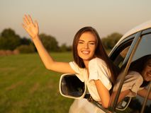 Happy woman in the car with raised hand on nature royalty free stock images