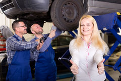 Happy woman at a car repair shop. Happy women at a car repair shop showing thumbs up while mechanics are examining her car's suspension in the background Stock Image