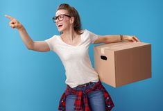 Happy woman with cardboard box pointing at something on blue stock photography