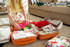 Happy woman is carefully packing clothes into suitcase. Happy woman is carefully packing colorful summer clothes into luggage suitcase for a new journey. Travel stock photos