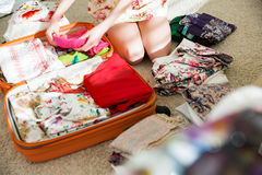 Happy woman is carefully packing clothes into suitcase Royalty Free Stock Photography