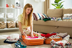 Happy woman is carefully packing clothes into suitcase Royalty Free Stock Photos