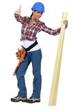Happy woman carpenter. With a plank of wood Stock Images