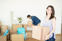 Happy Woman Carrying Box At New Home. Happy mid adult women carrying box while men doing arrangement in background at new home stock photography