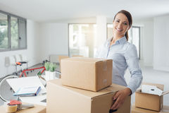 Happy woman carrying boxes into her new office Royalty Free Stock Photo