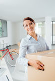 Happy woman carrying boxes into her new office Royalty Free Stock Photos