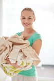 Happy woman carrying clothes to laundry at home Royalty Free Stock Image