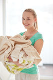 Happy woman carrying clothes to laundry at home Stock Image