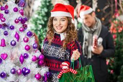 Happy Woman Carrying Shopping Bag In Christmas. Portrait of happy young women carrying shopping bag at Christmas store with men in background Royalty Free Stock Image