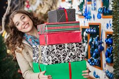 Happy Woman Carrying Stacked Gift Boxes In Store Stock Images