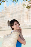 Happy woman carrying a straw shopping bag. Happy young woman carrying a straw shopping bag wearing a blue summer dress while on vacation Royalty Free Stock Image