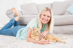 Happy woman with cat lying on rug. Full length of happy woman with cat lying on rug at home Royalty Free Stock Photography