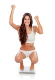 Happy woman celebrating her new weight on a scale Royalty Free Stock Photo