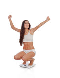 Happy woman celebrating her new weight on a scale Stock Photo
