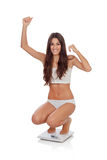Happy woman celebrating her new weight on a scale. On a white background royalty free stock photo