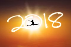 Happy woman is celebrating new year of 2018. Silhouette of happy woman dancing in the beautiful sunrise while while celebrating new year of 2018 Royalty Free Stock Image