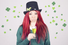Happy woman celebrating Saint Patrick's day on march 17th. Looking a little drunk with a glass a green beer, surrounded by shamrocks and clovers Royalty Free Stock Photo