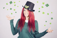 Happy woman celebrating Saint Patrick's day on march 17th. Smiling surrounded by shamrocks and clovers Stock Photography