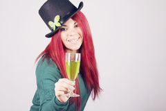 Happy woman celebrating Saint Patrick's day on march 17th. Toasting with a glass of green beer Royalty Free Stock Photo