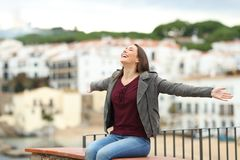 Happy woman celebrating stretching arms on a ledge. Happy woman celebrating day stretching arms on a ledge with a town in the background royalty free stock photos
