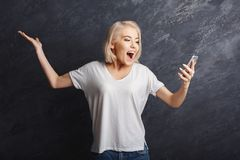 Happy girl reading good news on mobile. Happy woman celebrating success and reading good news on smartphone. Girl seeng exciting message on mobile at gray studio Stock Photo