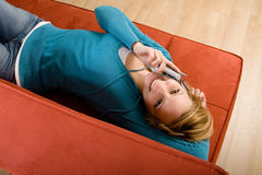 Happy woman on cellphone. Young woman talking on a cell phone with a happy expression while lying on a red couch Stock Images