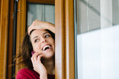 Happy woman on cellphone call at home window Royalty Free Stock Image