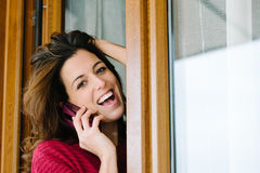 Happy woman on cellphone call at home window Stock Photos
