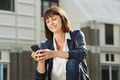 Happy woman with cellphone sitting outside Stock Photo