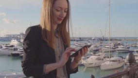Happy woman is chatting by phone with internet, reading messages and smiling stock video footage
