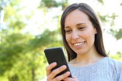 Happy woman checking smart phone message in a park. Happy woman checking smart phone message standing outdoors in a park stock images