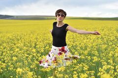 Happy woman cheering in canola field in the summer Royalty Free Stock Images