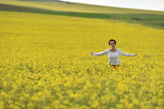 Happy woman cheering in canola field in the summer Royalty Free Stock Photography