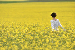 Happy woman cheering in canola field in the summer Royalty Free Stock Image