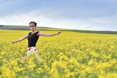 Happy woman cheering in canola field in the summer Stock Images