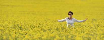 Happy woman cheering in canola field in the summer Royalty Free Stock Photo