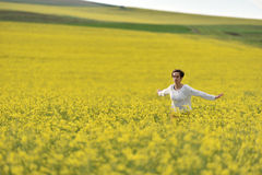 Happy woman cheering in canola field in the summer Stock Photography