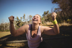 Happy woman cheering during obstacle course. In boot camp royalty free stock image