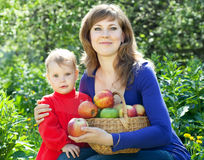 Happy woman and child apples in garden Royalty Free Stock Images