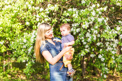Happy woman and child in beautiful spring blooming garden. Family holiday concept. Mothers day Royalty Free Stock Photos