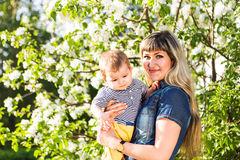 Happy woman and child in beautiful spring blooming garden. Family holiday concept. Mothers day Stock Photo