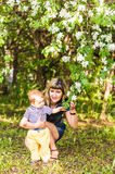 Happy woman and child in beautiful spring blooming garden. Family holiday concept. Mothers day Stock Image