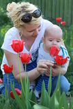 Happy woman and child with beautiful spring flowers against green background. Stock Photography