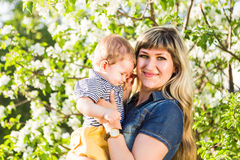 Happy woman and child in the blooming spring garden.Mothers day holiday concept Stock Images
